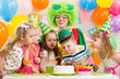 kids with clown celebrating birthday party and blowing candles o