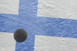 Finnish flag and the puck on the ice