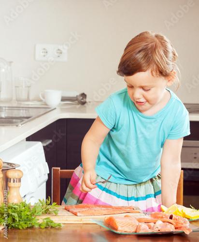 baby girl cooking salmon