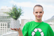Happy pretty environmental activist showing a plant