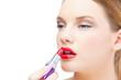 Glamorous blonde model applying red lipstick
