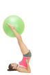 Content sporty brunette holding exercise ball between legs