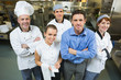 Handsome manager posing with some chefs and waitress