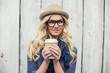 Pensive fashionable blonde holding coffee outdoors