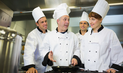 Experienced head chef explaining food to his colleagues