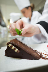 Close up of chef putting mint leaf on chocolate dessert