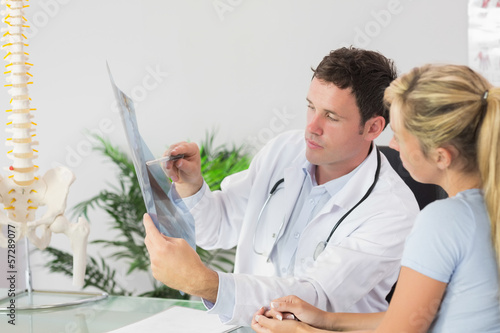 Handsome doctor showing a patient something on x-ray