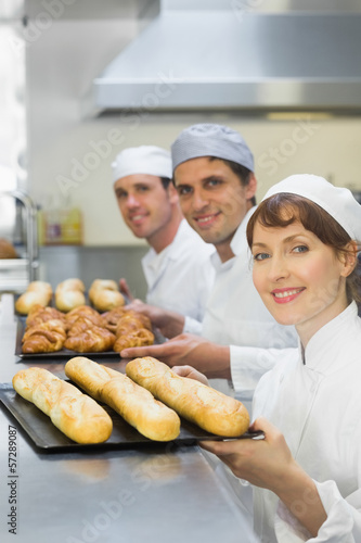 Three young bakers holding baking trays