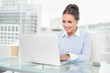Smiling brunette businesswoman typing on laptop