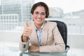 Smiling businesswoman showing thumb up at her desk