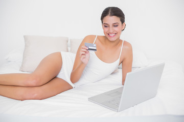Happy young brown haired model in white pajamas shopping online