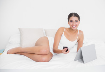Pretty young brown haired model in white pajamas holding a mobil