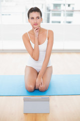 Thoughtful natural brown haired woman in white sportswear posing