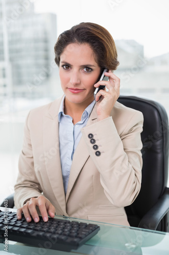 Stern businesswoman phoning