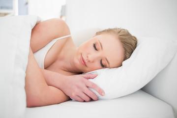 Natural peaceful blonde sleeping in bed