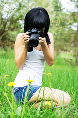 the girl photographs a dandelion