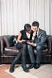 Couple of businessman and woman looking at tablet sit on a sofa.
