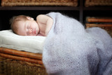 baby sleeping on a wicker chest
