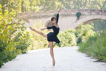 Young beautiful ballerina dancing in Tevere riverside in Rome, I