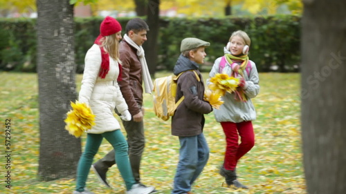 Happy family of four having fun in the park in autumn