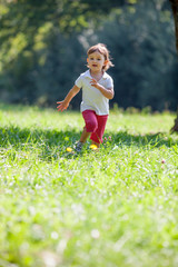 fun two year-old baby running in green environment