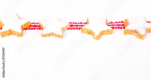 Zimtsterne und Geschenkband auf weiß