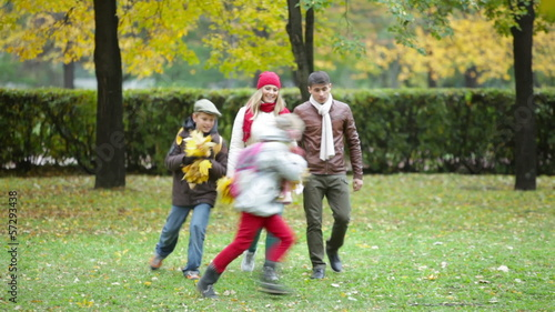 Playful kids and their parents walking in the park