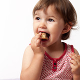 baby girl eating with pleasure and fun at two years old poster