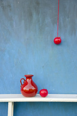 red beautiful ceramic pitcher anr two apples