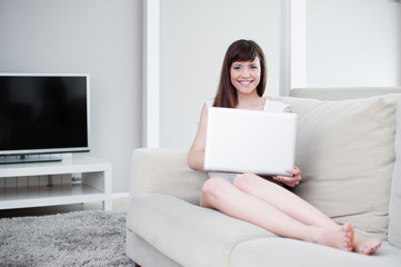 A beautiful woman using her laptop in her living room.