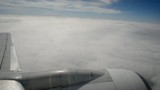 Clouds under wing of an airplane during climb.