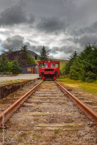 Old train waiting on railway station under dramatic sky.