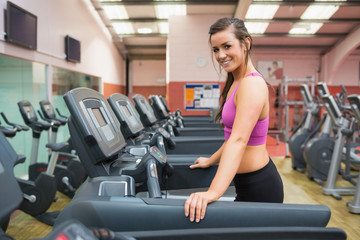 Smiling woman on a treadmill in the gym taking a break