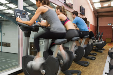 Four people riding exercise bikes