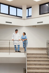 Nurse and doctor having a discussion at top of stairwell