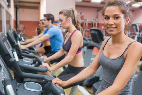 Smiling woman with other people riding an exercise bike