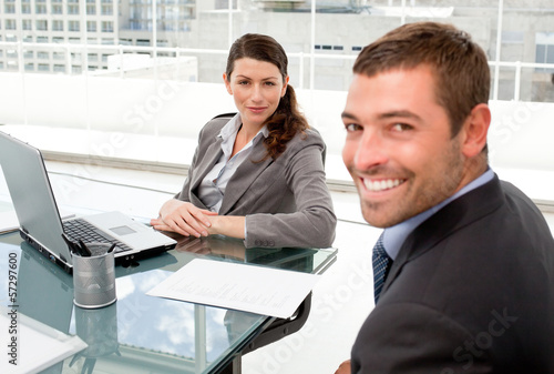 Happy businessman and businesswoman working together on a laptop
