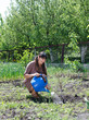 Happy woman tending to her vegetable garden