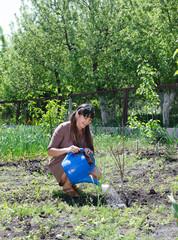 Happy woman tending to her vegetable garden