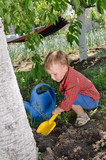 Cute little boy digging in the garden