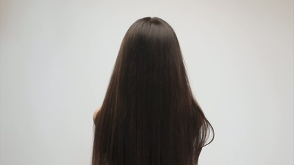 Young woman gently touching her long hair