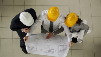 Group of three architects discussing project of new construction