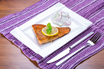 Grilled trout with lemon on the plate