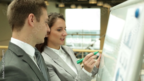 Businesswoman explaining marketing analysis to her colleague