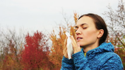 Sick woman blowing her nose into tissue, outdoors