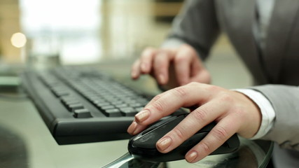 Young female hand on computer mouse during typing on keyboard