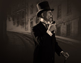 Man 1900 style smoking a pipe wearing black hat and coat. Dicken