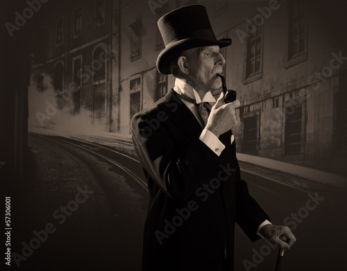 Man 1900 style smoking a pipe wearing black hat and coat. Dicken - 57306001
