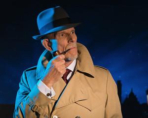 Retro detective man smoking pipe walking in city street at night
