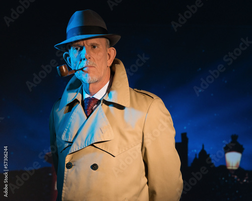 Retro detective man smoking pipe walking in city street at night